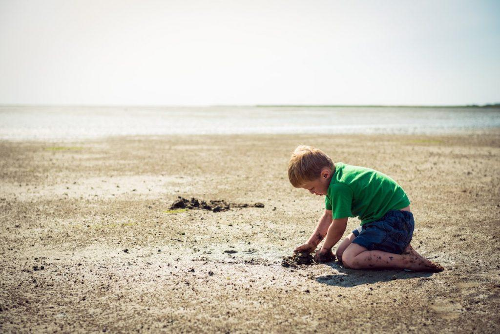 Boy playing in the mud flats. © KV Juist